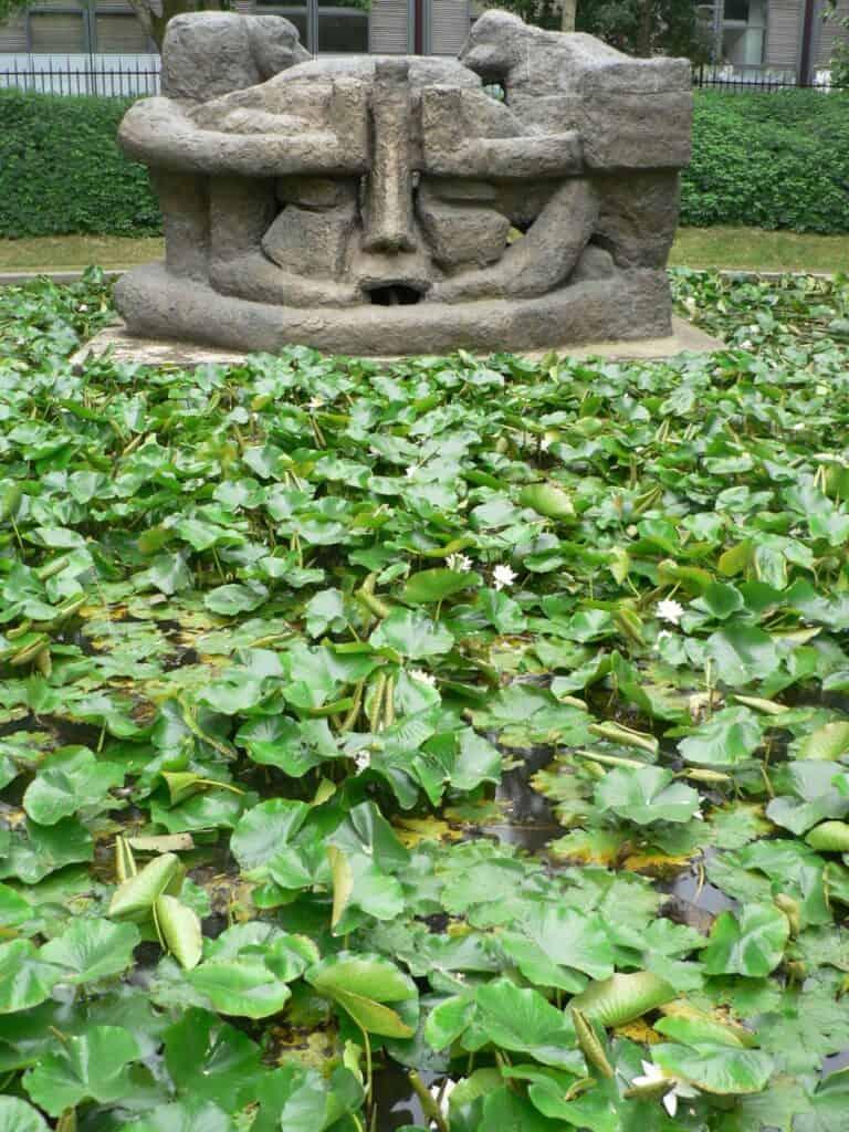 Sculpture de casque de Maya devant mare de nénuphars.